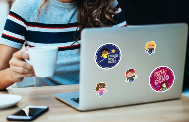 Image of a young woman with a cup of tea and a laptop featuring several stickers on its lid of graphics designed by Design102 in the Journey into the Known GCHQ recruitment campaign branding.