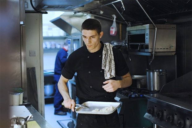 Image of Tyler, a Greene King chef and ex-offender, working in a kitchen