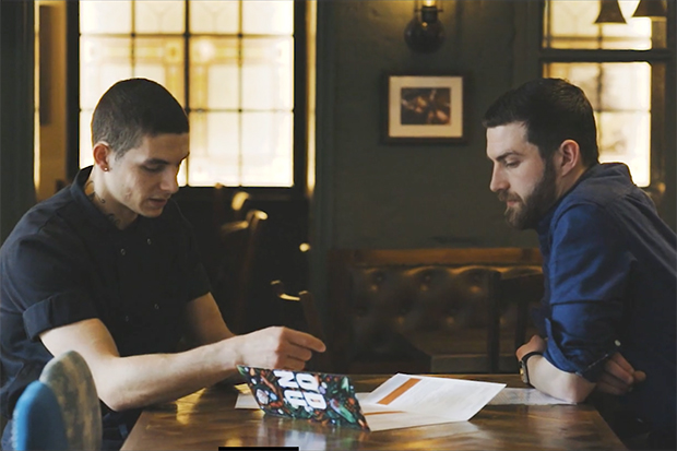 Image of Tyler, a Greene King chef and ex-offender, sitting at a pub table opposite his assistant manager Sam Calver, discussing work.