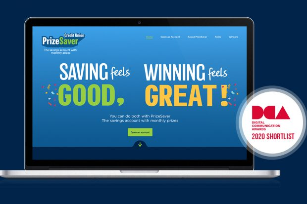Image of the PrizeSaver website homepage on a laptop screen. The background is blue with small confetti decorations. The homepage reads 'Saving feels good. Winning feels great. You can do both with PrizeSaver, the savings account with monthly prizes'