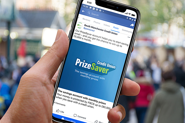 A photograph of a hand holding a smartphone showing a PrizeSaver Facebook advert. The Facebook caption reads: 'Our PrizeSaver account helps you to start saving small - and you get the chance to win up to £5,000 a month'