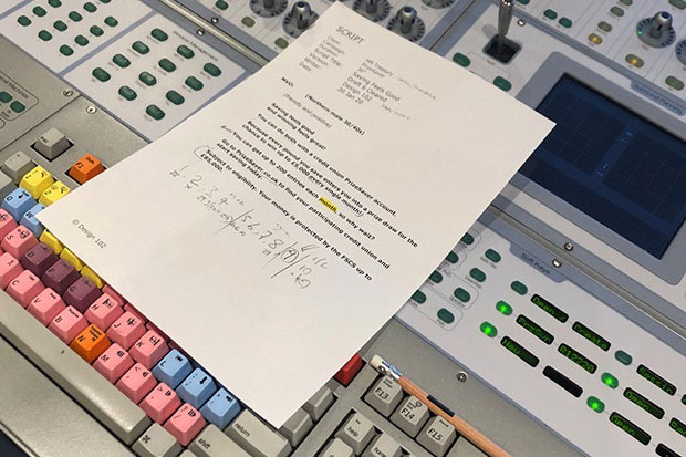 A white piece of A4 paper covered in unintelligible writing. This is the script for the radio advert. Scribbles and corrections are visible written in the margins. The paper is placed on top of a recording studio's control dashboard with multicoloured buttons