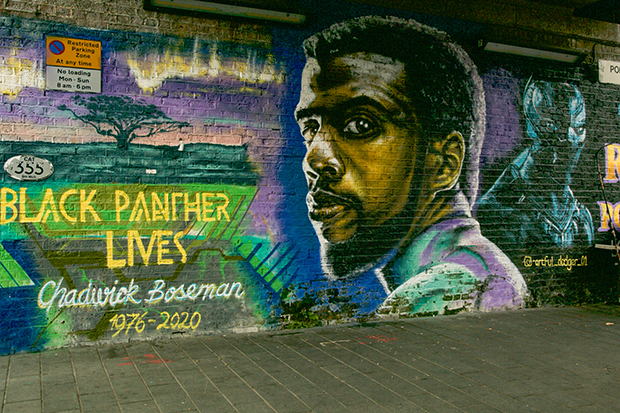Mural painted on a brick wall at street level. It depicts the actor Chadwick Boseman looking at the viewer, alongside the words 'Black Panther lives, Chadwick Boseman, 1976 to 2020'.