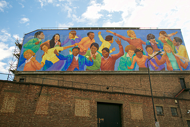 Mural painted on the side of a brick building. The mural depicts 18 children of different races running, playing and holding each other. The background is bright blue and their clothing is colourful: purple, yellow, red and orange.