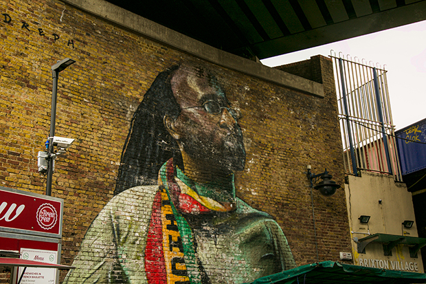 Mural painted on a brick wall beneath a railway bridge. The mural depicts Michael Johns, a local resident. Johns has long dreadlocks and small round glasses. In the painting he looks calmly upward while wearing a green t-shirt and red, yellow and green scarf.