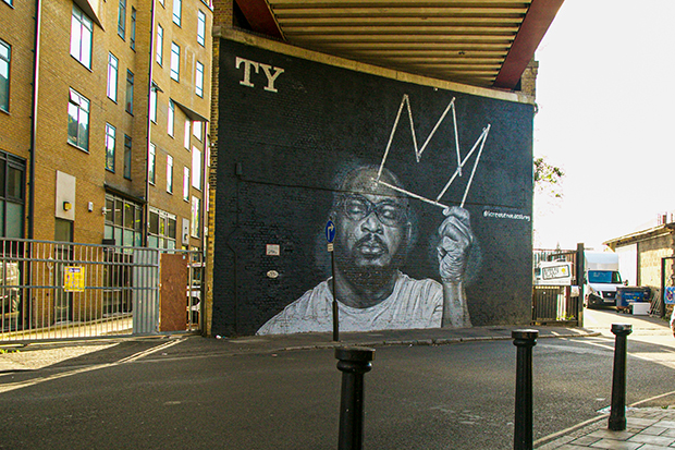 Mural painted on a brick wall at street level, beneath a railway bridge. The mural depicts the rapper TY, who died in 2020. It is a black-and-white painting. TY has his eyes closed and holds the outline of a crown in one hand.